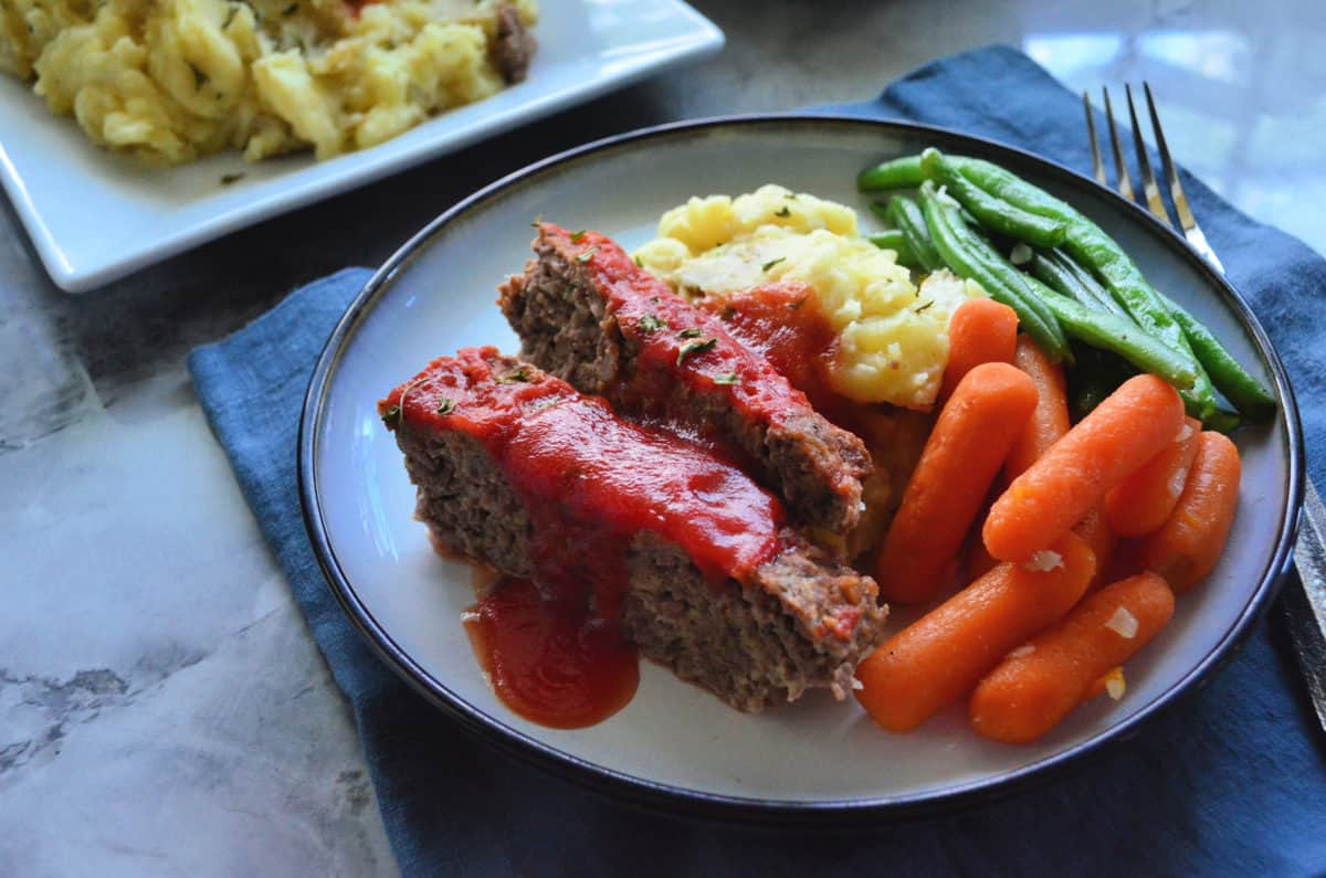 Plated Slices of meat loaf served with carrots, green beans, and mashed potatoes.