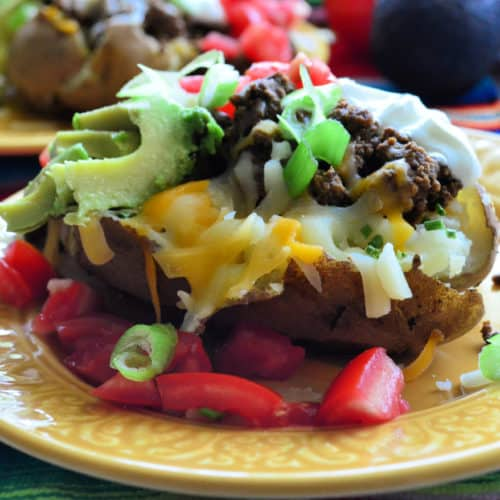 Side View Plated Baked potato loaded with sour cream, tomato, olives, avocado, and shredded cheese.