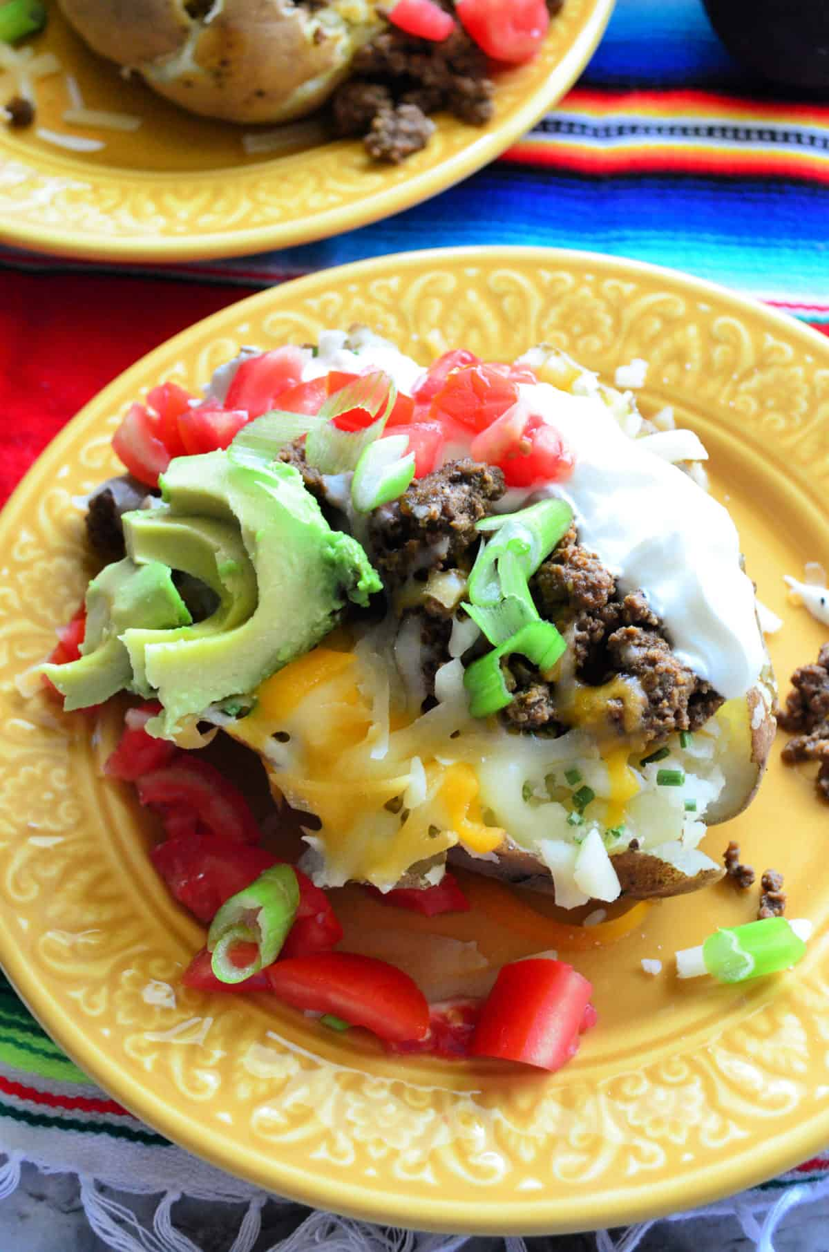 Top view split baked potato with sour cream, meat, tomato, cheese, avocado, green onions on plate.