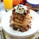 Plated Chocolate Chip pancakes stacked high, topped with pecans, chocolate chips, whipped cream, and caramel sauce.