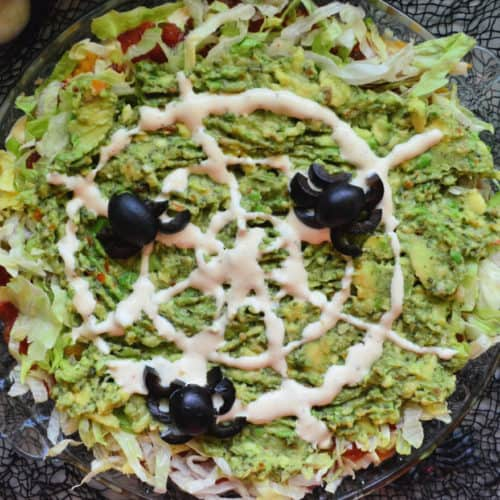 Guacamole Dip topped with Olives arranged to look like spiders and dressing to look like web.