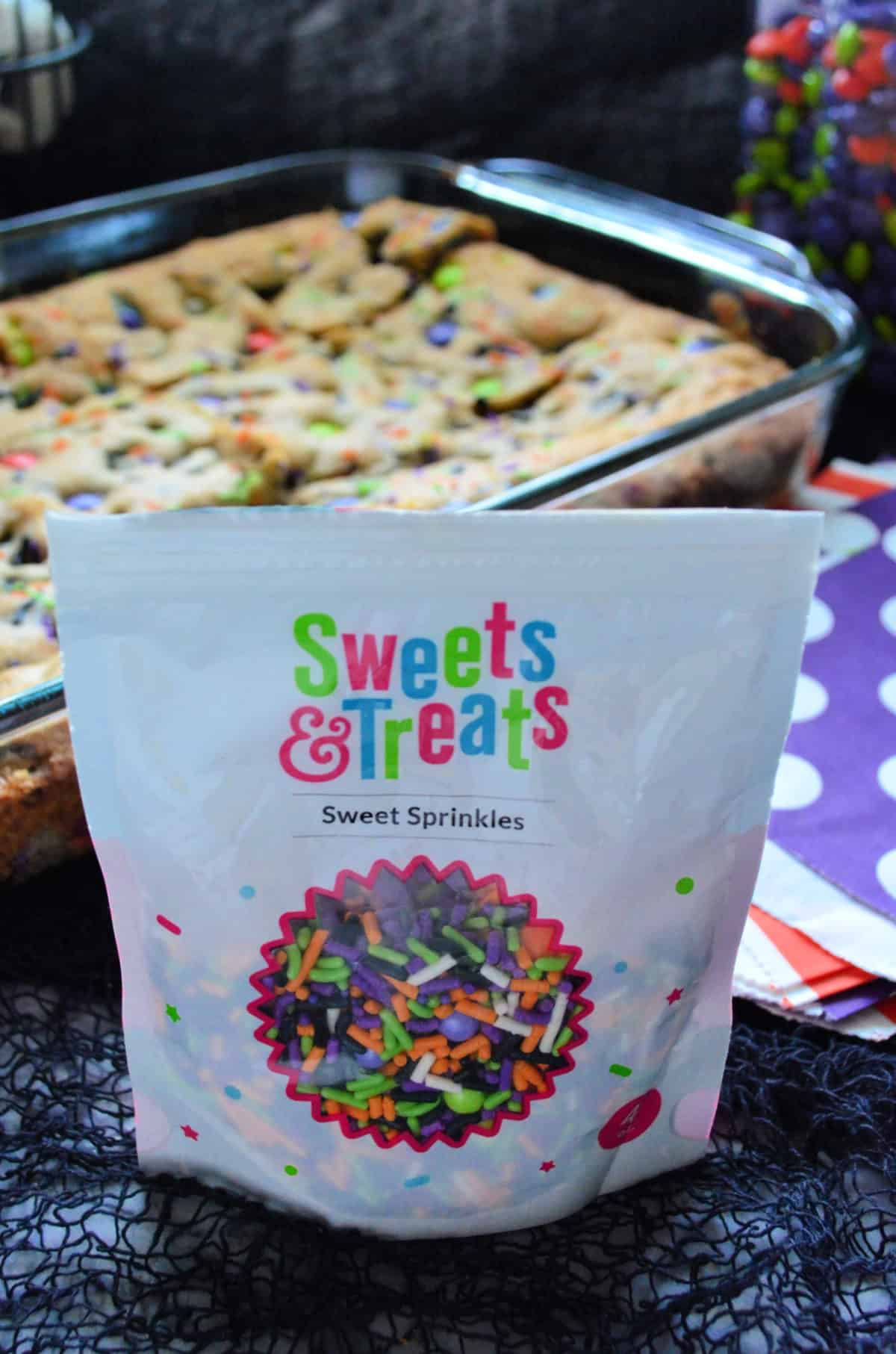 Bag of Sweets & Treats Sprinkles in orange, green, and purple with cookie bar in background.