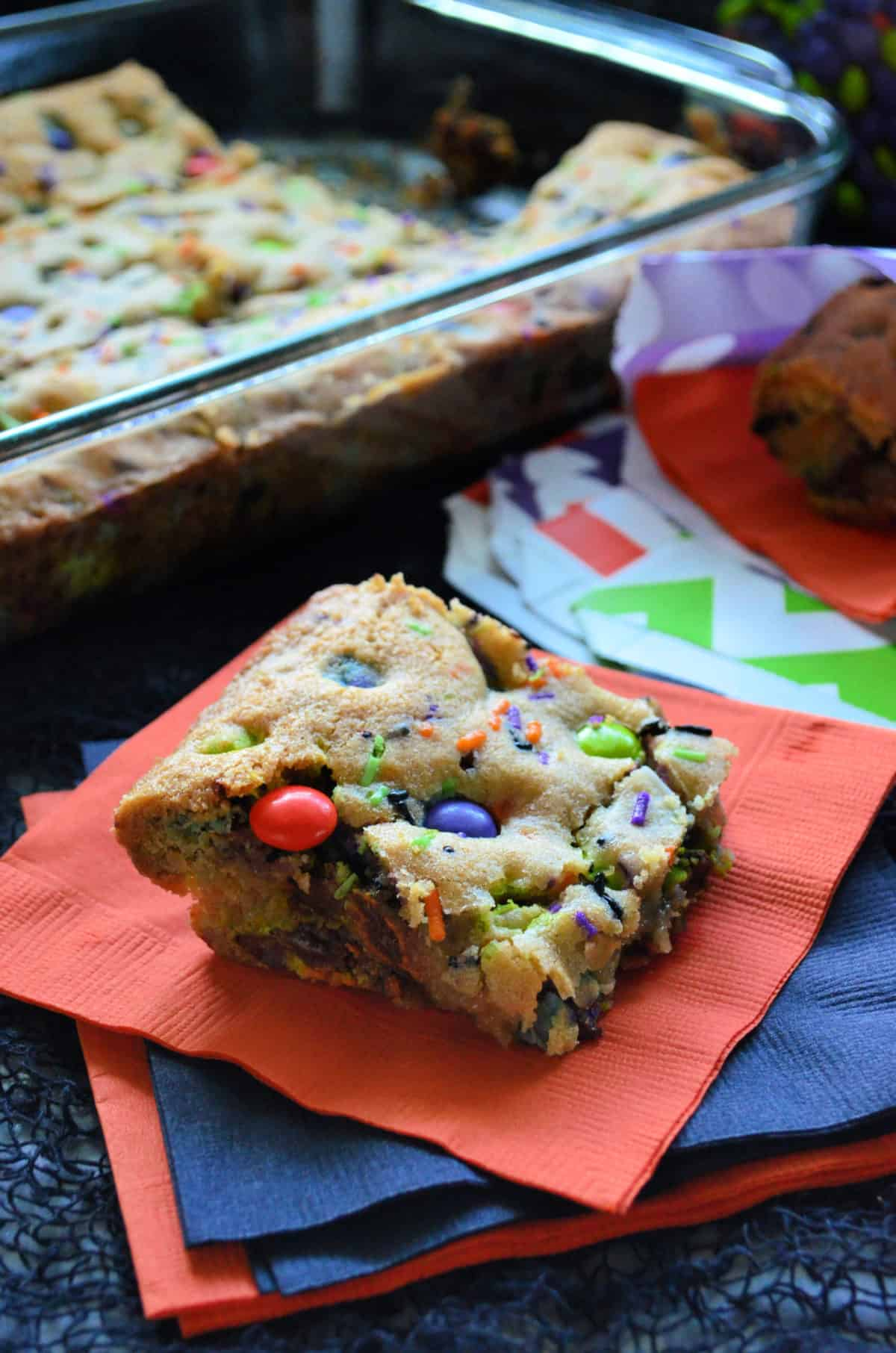 cookie bar square made with orange, purple, and green M&Ms and sprinkles on orange napkin.
