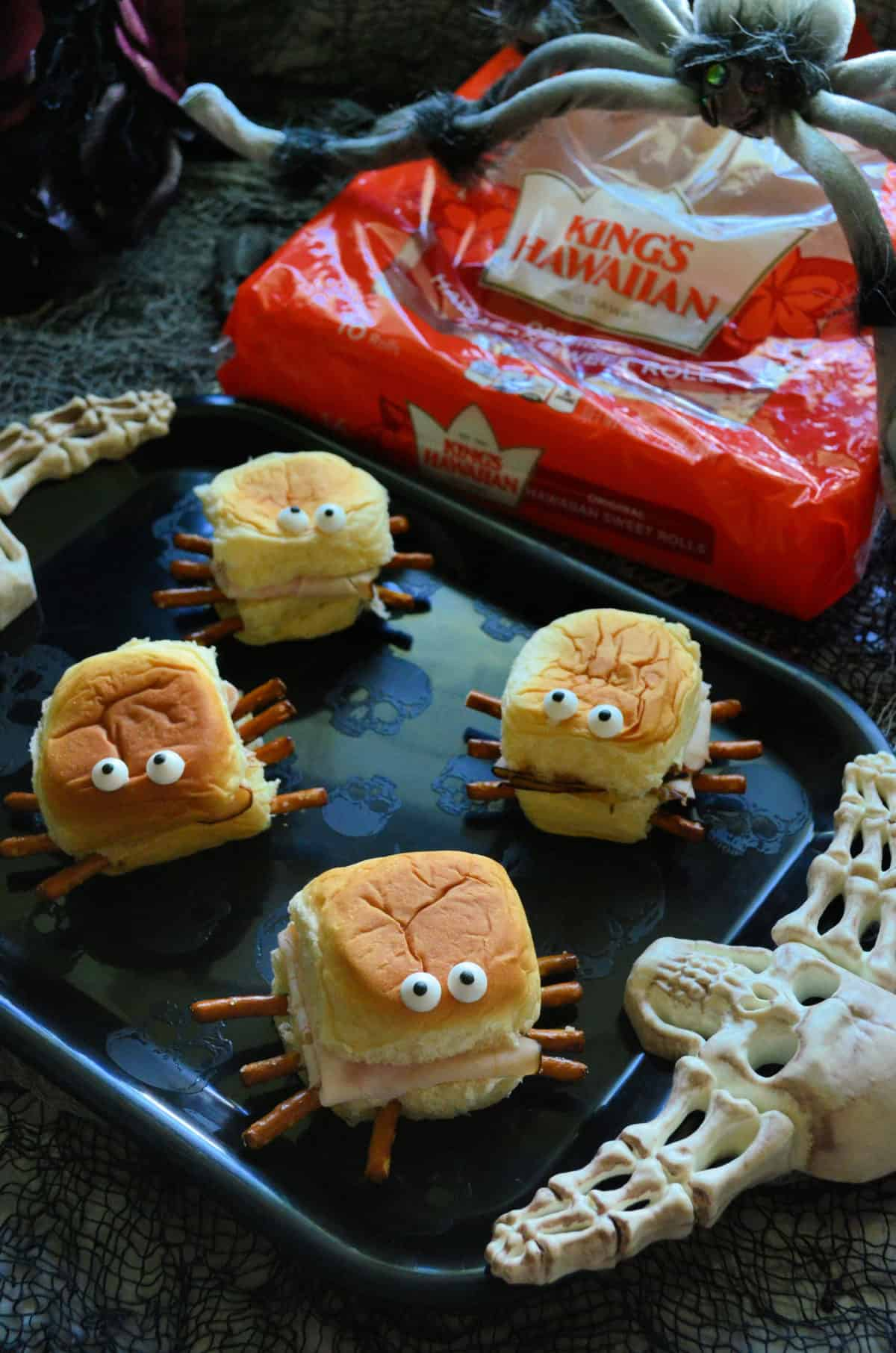 King's Hawaiian rolls with turkey, pretzels sticking out like spider legs, and candy eyes on top.
