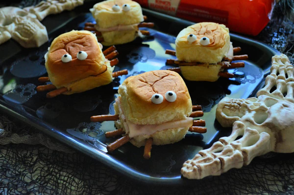 closeup of small turkey sandwiches with pretzels sticking out like spider legs, candy eyes on top.