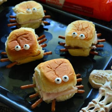 Close up of 4 Halloween Turkey & Cream Cheese Spider Sandwiches on black plate.