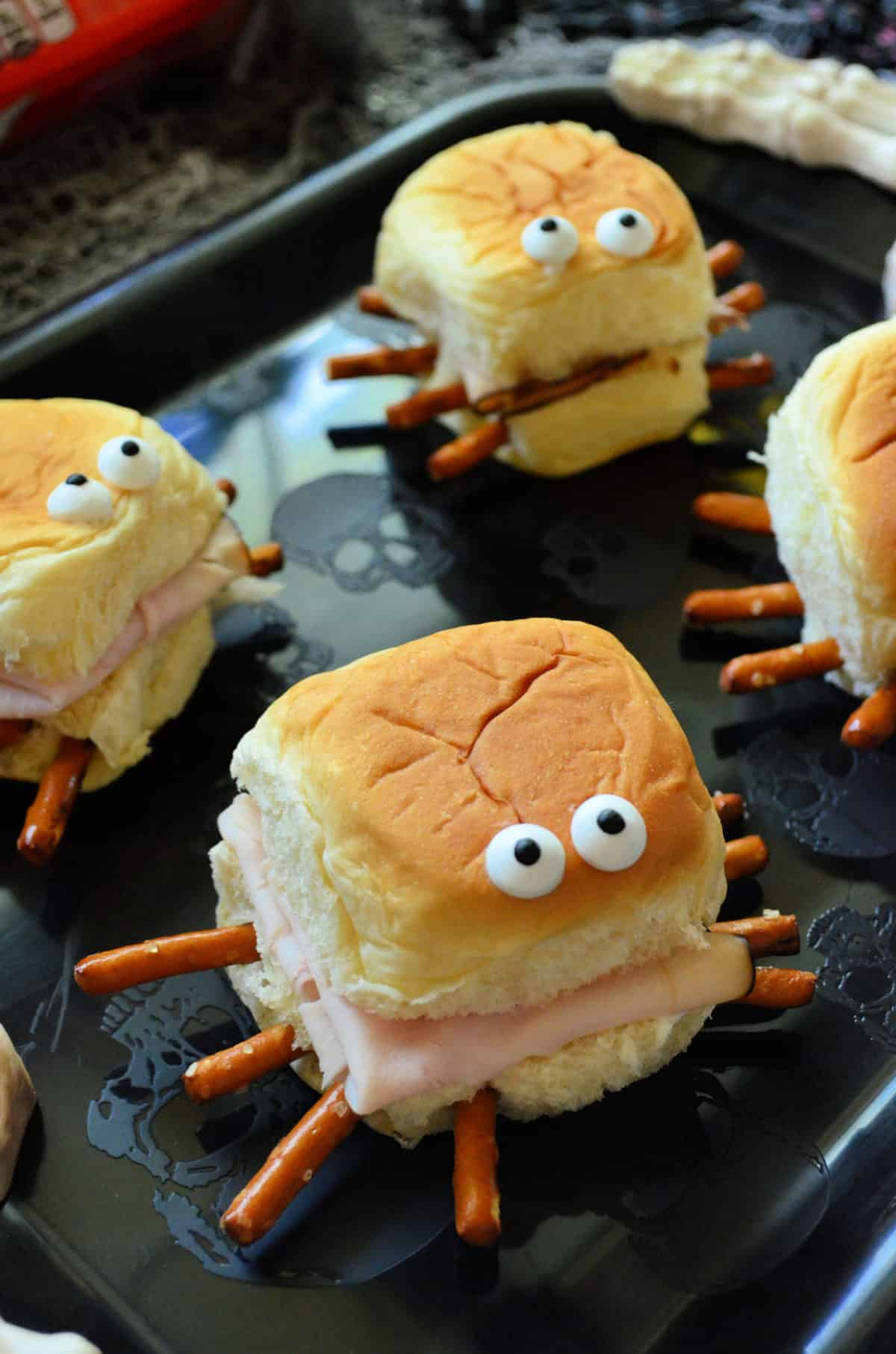 closeup of small rolls with turkey, pretzels sticking out like spider legs, and candy eyes on top.