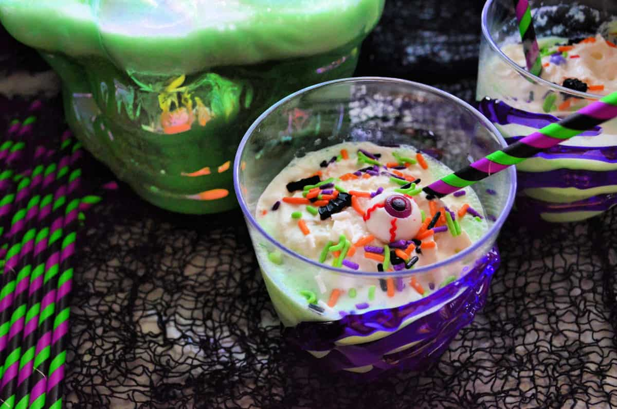 2 cups of creamy green liquid topped with whipped cream, sprinkles, and candy eyeballs on black gauze.
