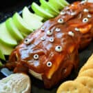 Closeup of sliced apples, crackers, and caramel cream cheese dip decorated with candy eyes.