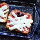 marinara, mozzarella, and black olives topping toast to look like mummy face in spider web dish.