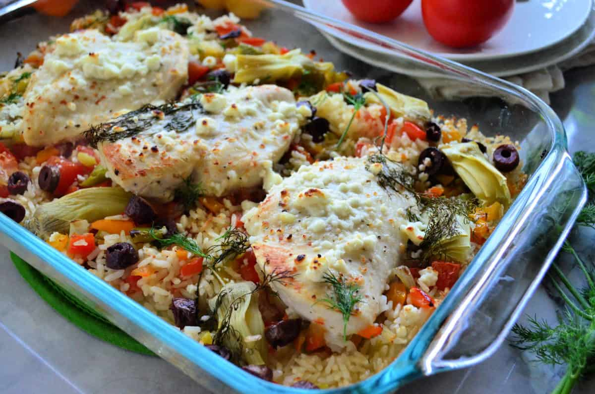 chicken over bed of rice with artichoke, bell pepper, kalamata, tomatoes, and dill in casserole dish.