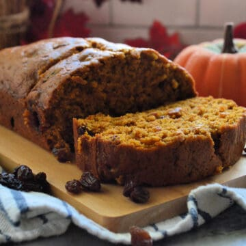 Pumpkin Bread with Raisins resting on board with one slice lying horizontal near mini pumpkin.
