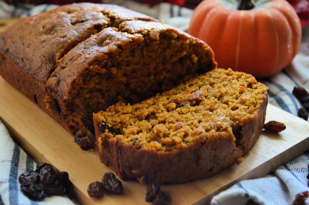 closeup pumpkin bread with raisins on paddle with 2 pieces sliced in front of decorative pumpkin.