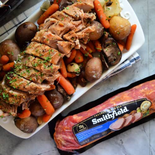 Plated Pork Tenderloin on bed of carrots and potatoes next to package of Smithfield.