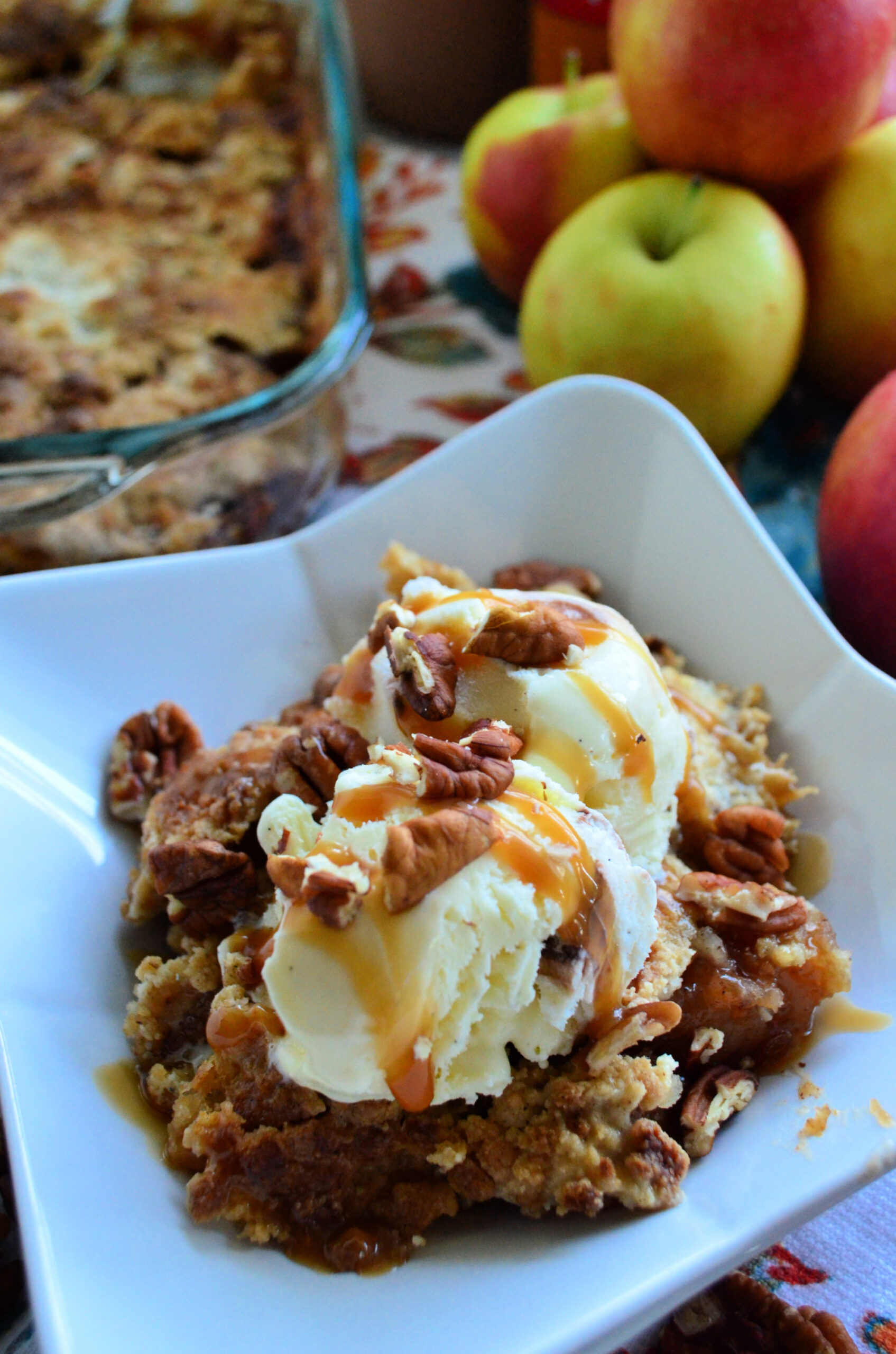 Close up Apple Dump Cake topped with vanilla ice cream, pecans, and caramel drizzle.
