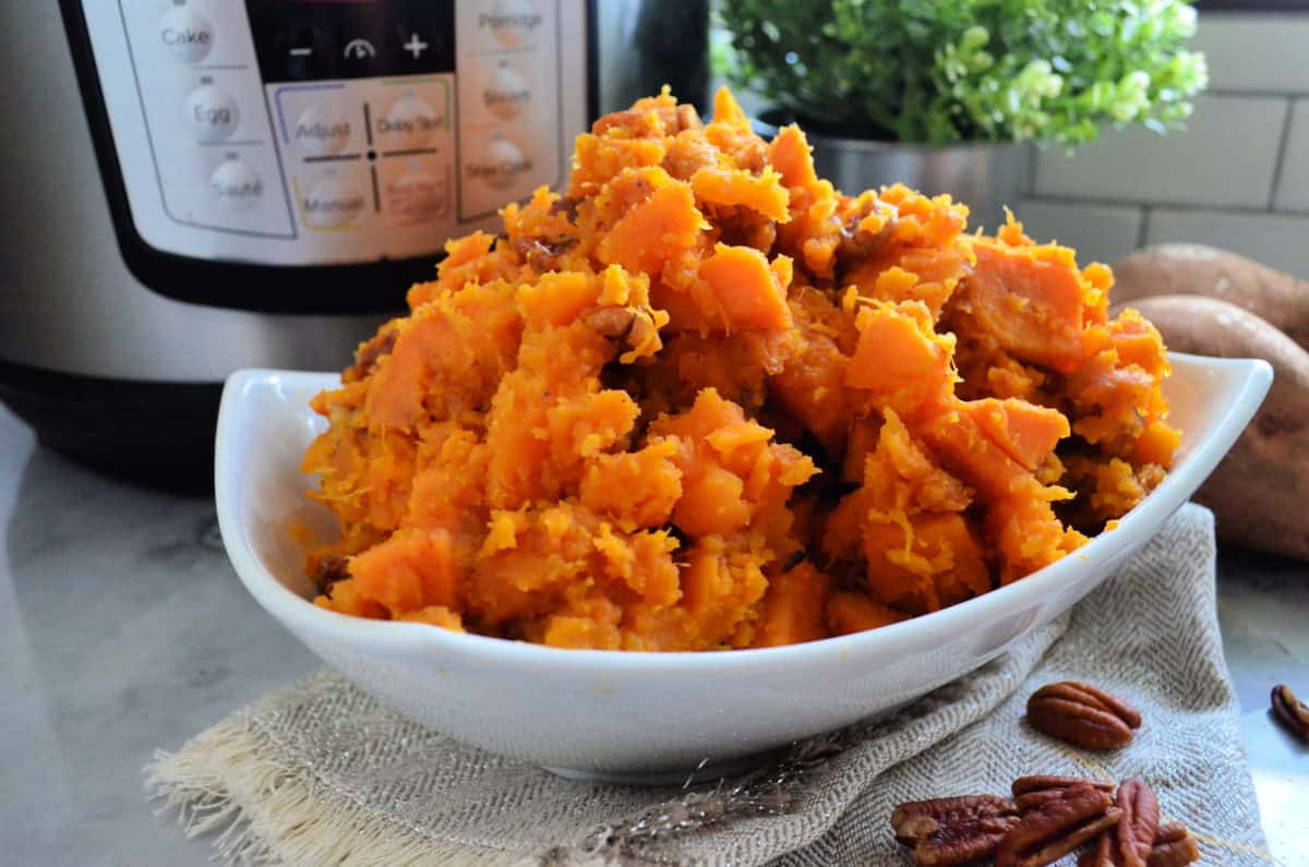 side view of dish of sweet potatoes in dish in front of instant pot next to pecans.