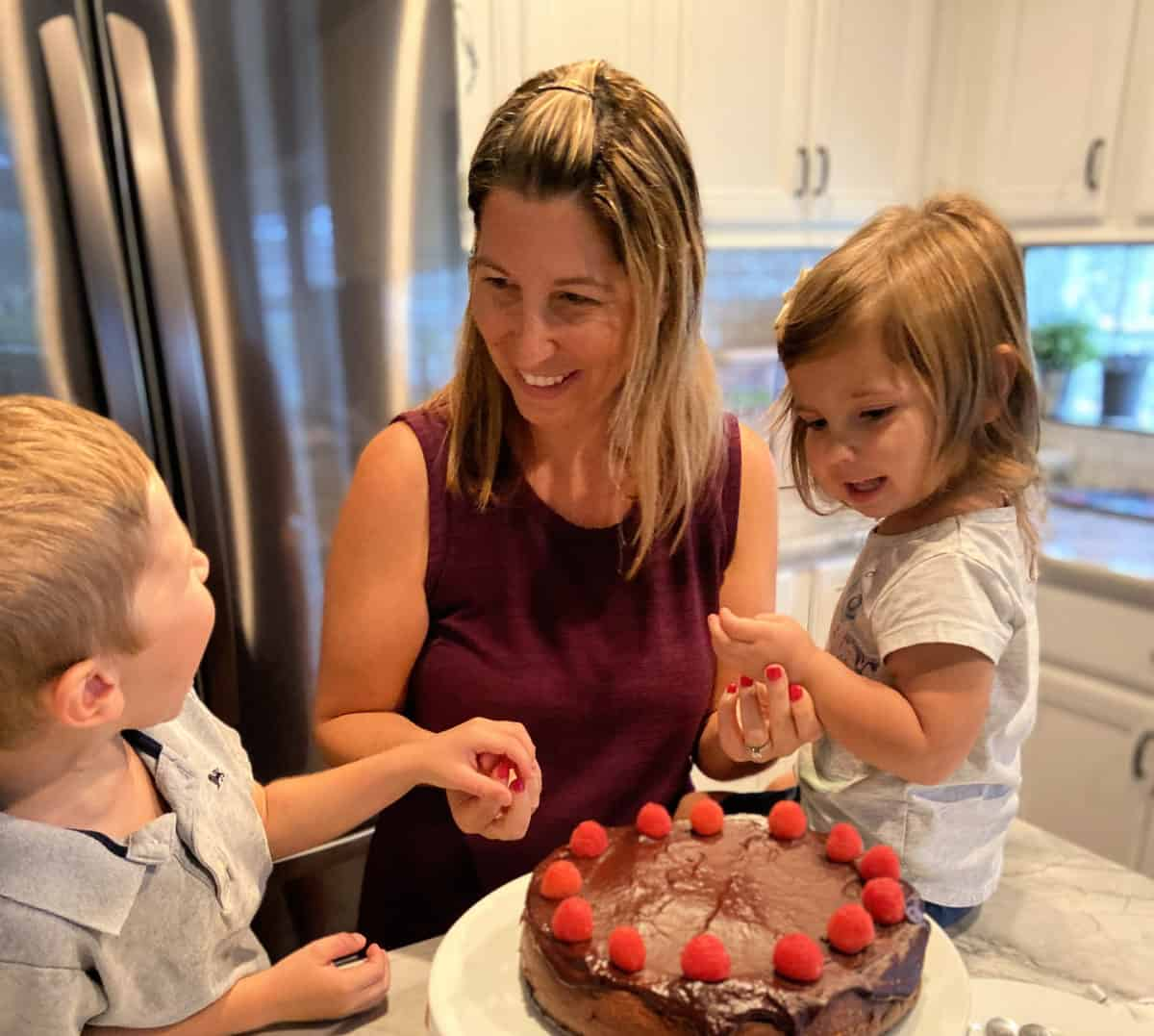 Mother, daughter, and son, decorating dark chocolate covered cake with raspberries at counter.
