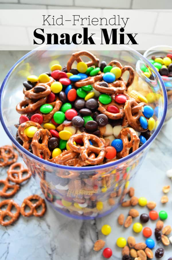Glass of M&Ms, pretzels, popcorn, and peanuts with pinterest title text.