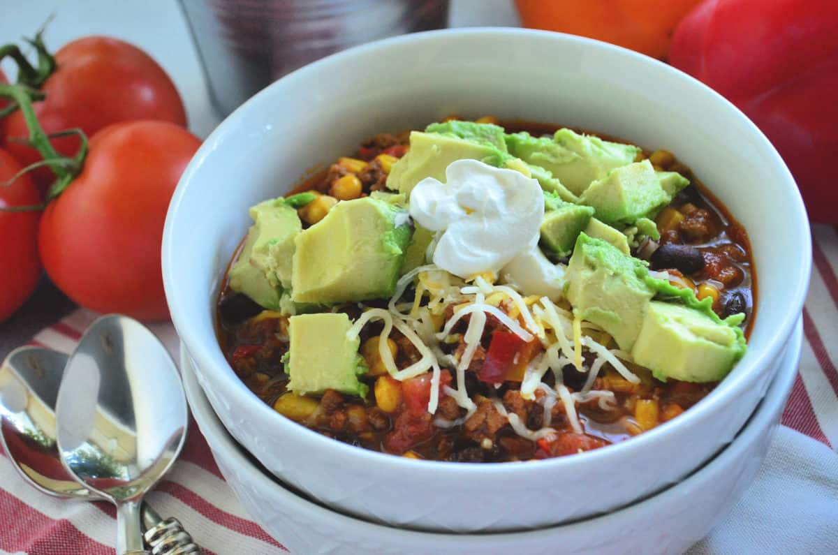 bowl of chili topped with avocado and shredded cheese on tablecloth with spoons and tomatoes.