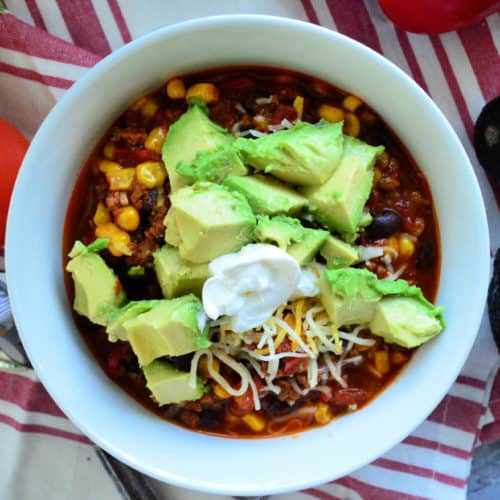 Top view of chili in bowl topped with sour cream, shredded cheese, avocado.