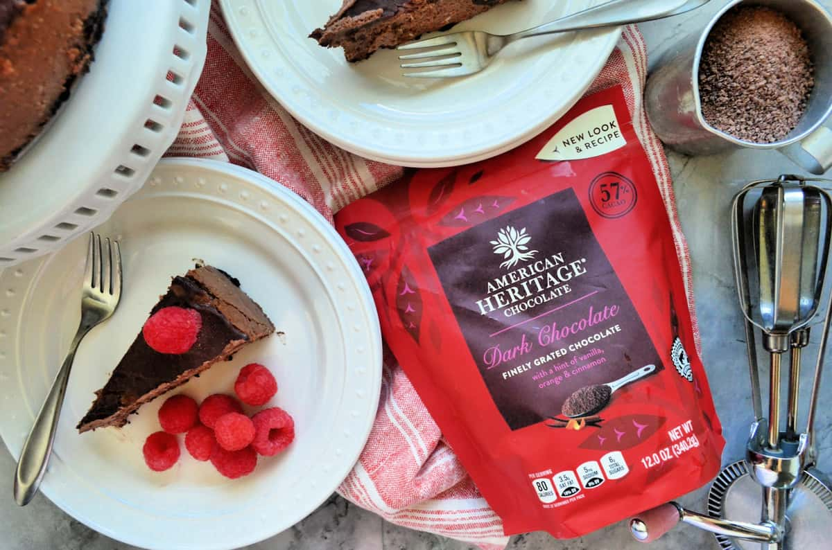 American Heritage Chocolate package next to plated cheesecake with raspberries, cup of brown powder, and whisk.
