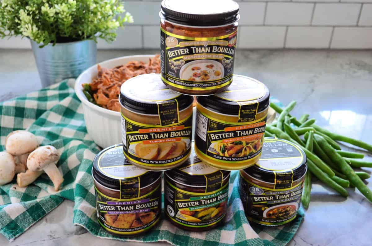 6 jars containing different flavors of Better Than Bouillon stacked n pyramid on checkered cloth.