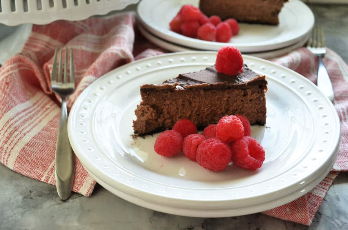Plated slice of dark chocolate cheesecake with fresh raspberries on red tablecloth with forks.