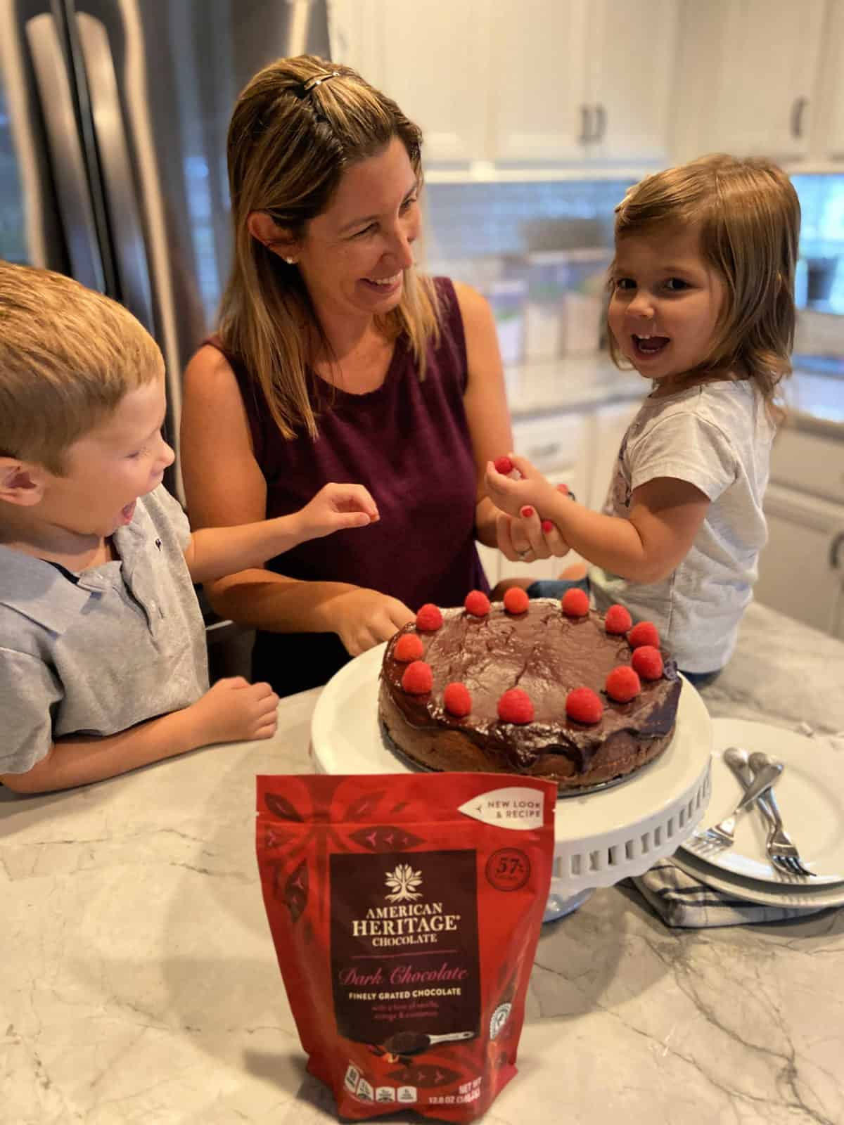 Mother, Daughter, and Son decorating chocolate cheesecake with fresh raspberries.