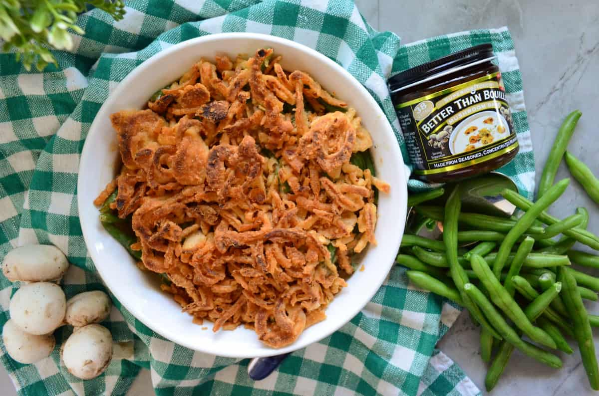 casserole dish with french fried onions next to green beans, mushrooms, and better than bouillon.