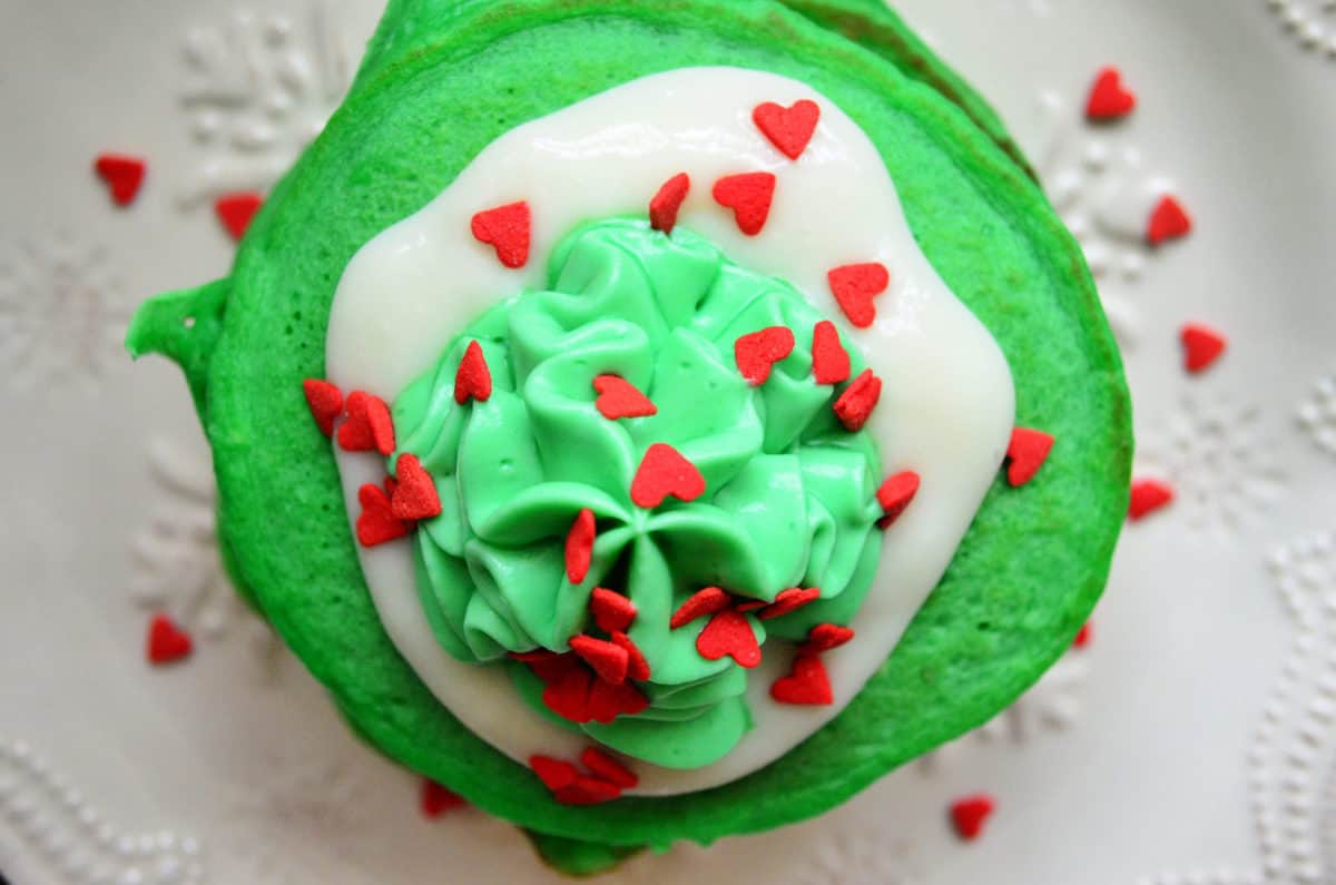 Top view of green pancakes with white icing, green whipped cream, and red heart sprinkles.