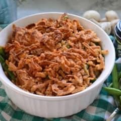 Casserole Dish of Green Bean Casserole Topped with Crispy French Fried Onions on top of tablecloth.