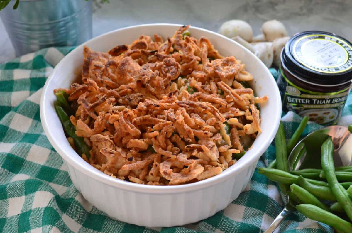 round casserole dish with green bean casserole topped with crispy onions next to green beans.