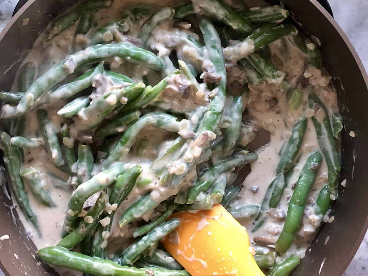 top view of green beans in pan being stirred with white sauce and chopped mushrooms with spatula.