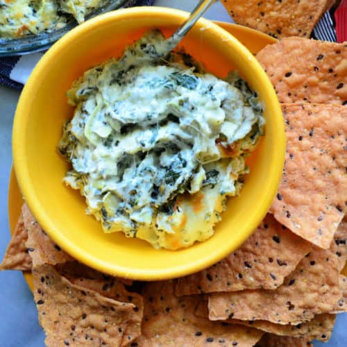 Spinach Artichoke Dip inn yellow bowl with spoon served with chips on the side.