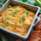 Buffalo chicken dip in a ceramic baking dish garnished with green onion and melted cheddar.