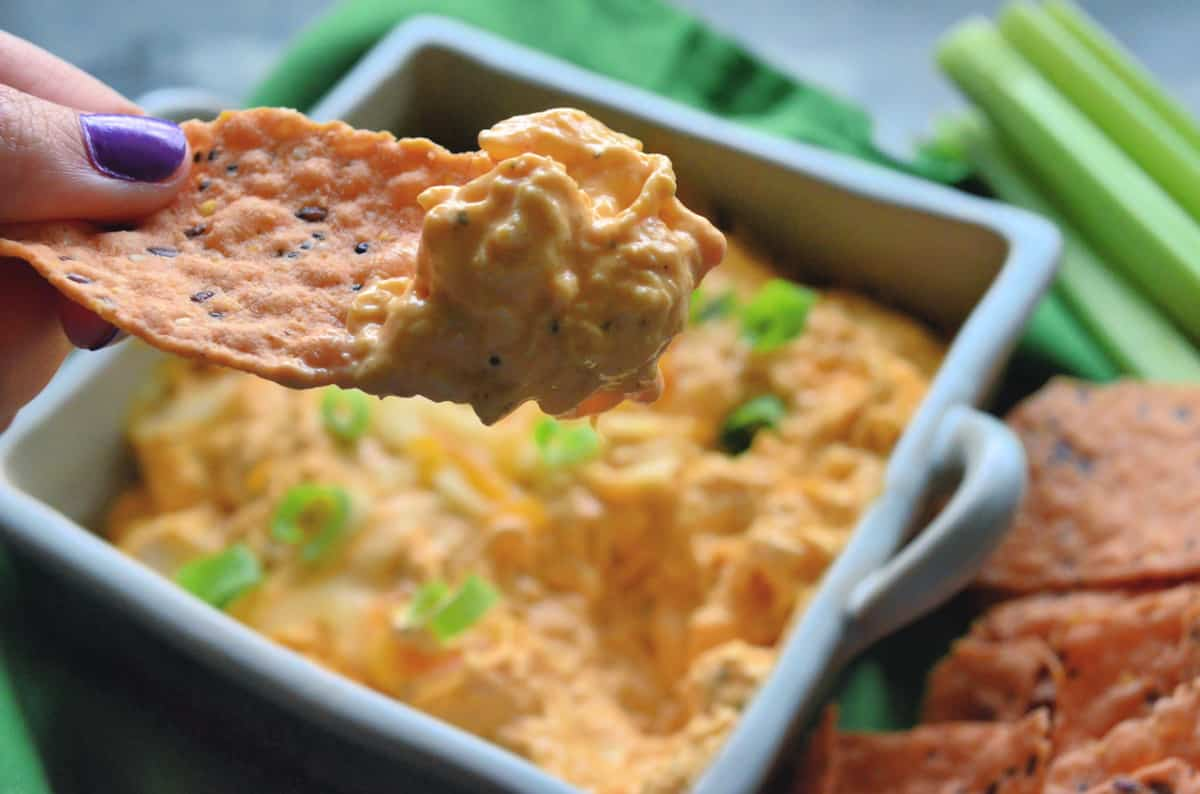 hand holding chip dipped in cheesy buffalo chicken dip with dip, celery, and chips in background.