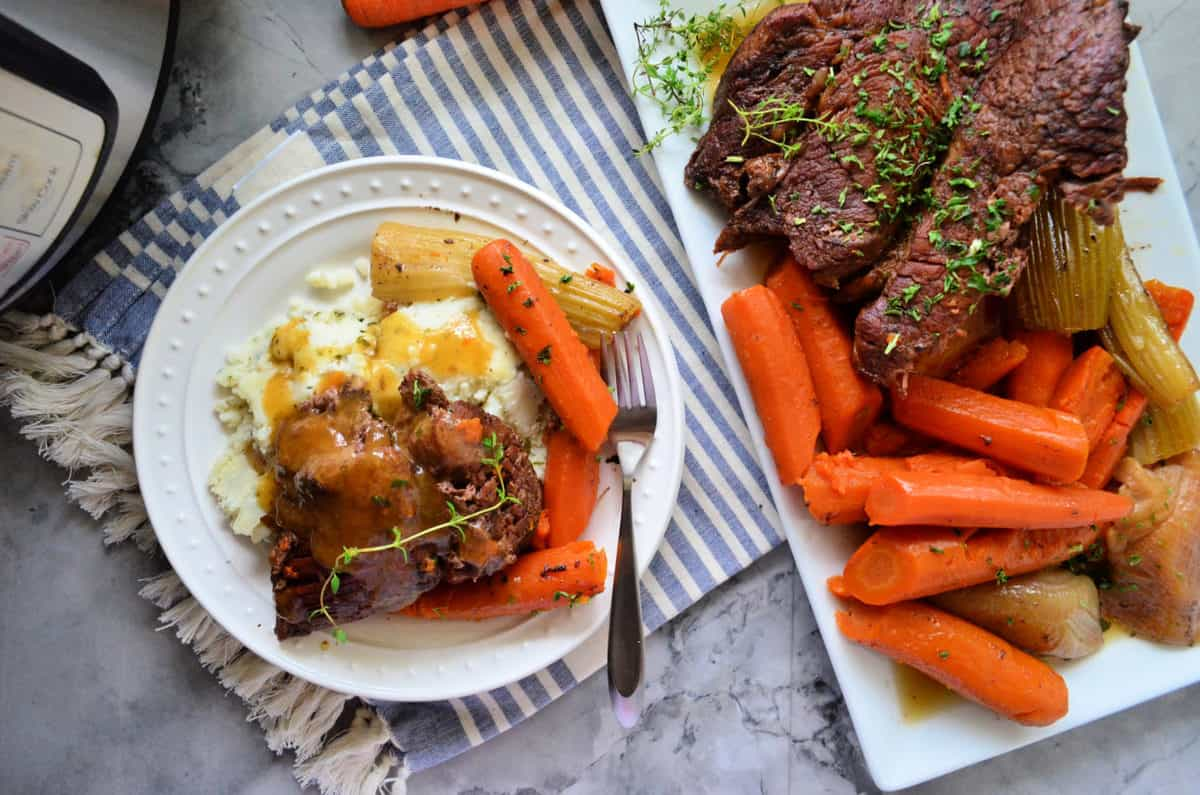 Plated Pot roast with mashed potatoes, celery, carrots, and gravy next to serving platter.