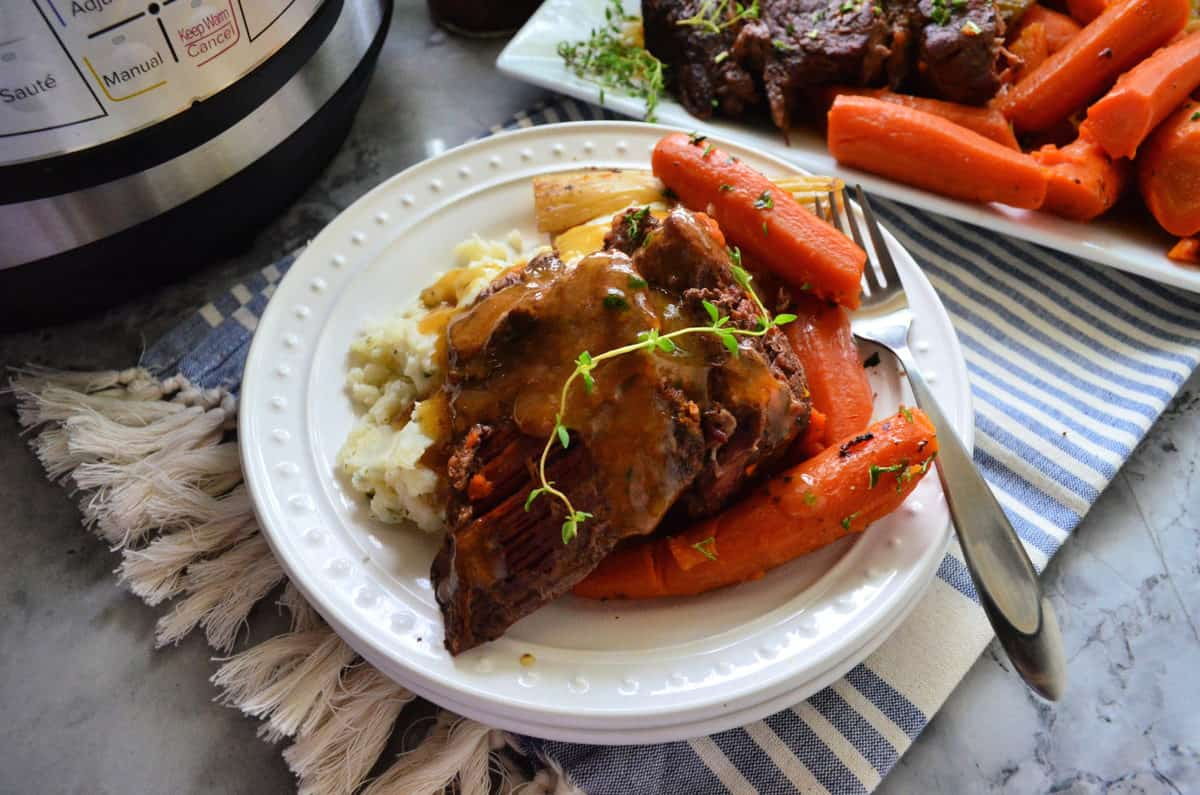 plated pot roast and carrots over bed of mashed potatoes with fork on placemat.