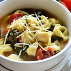 Bowl of tortellini, spinach, tomato, broth, and shredded cheese.