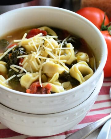 Two bowls stacked in front of vine ripened tomatoes. Top bowl filled with spinach tortellini soup.