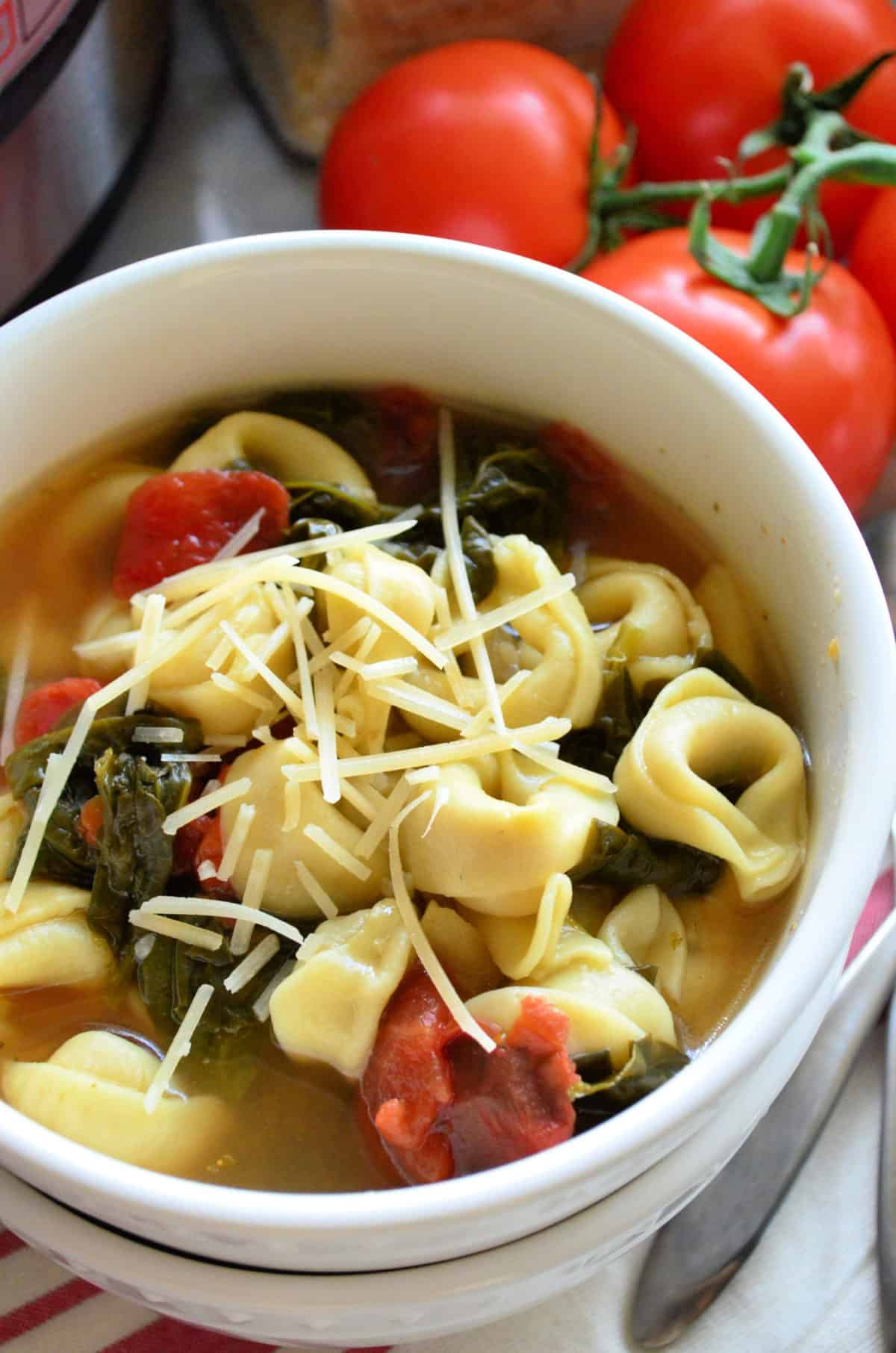 close up top view of bowl filled with broth, tortellinis, tomatoes, spinach, and topped with shredded cheese.