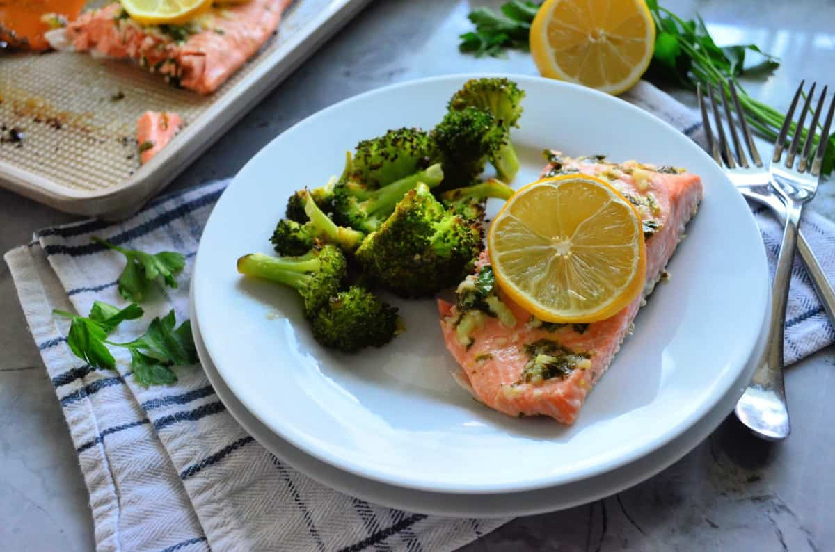 Plated cooked salmon topped with lemon wheel served with roasted broccoli next to forks.