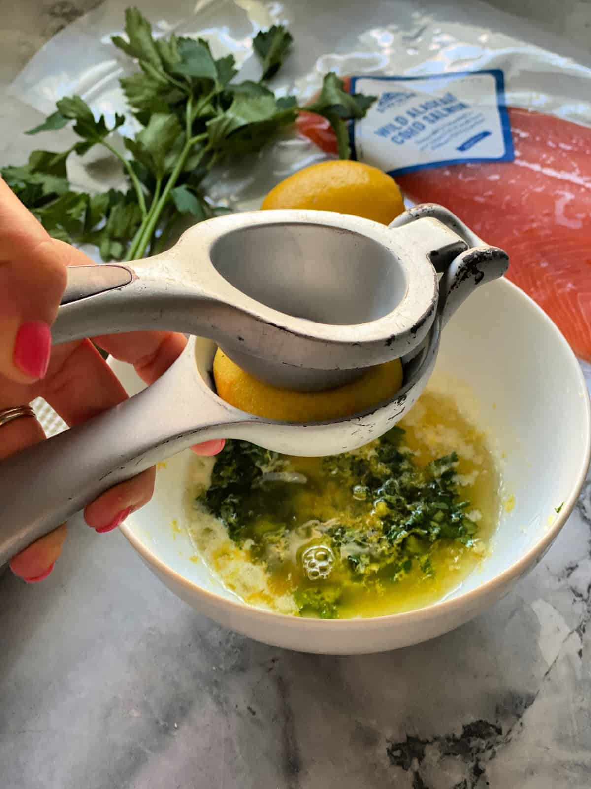 Hand using press to juice lemon into bowl with butter and parsley next to package of salmon.