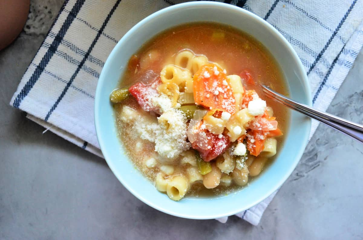 top view bowl of soup with pasta, broth, carrots, onions, celery, and tomato topped with parmesan.