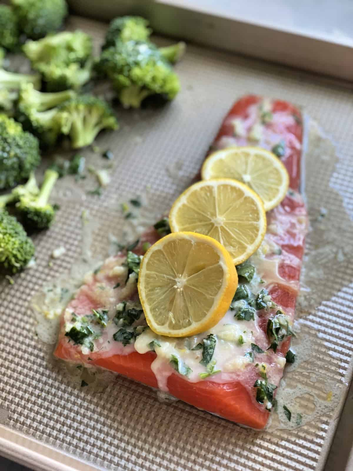 sheet pan with salmon topped with white herb sauce and lemon wheels prior to cooking.