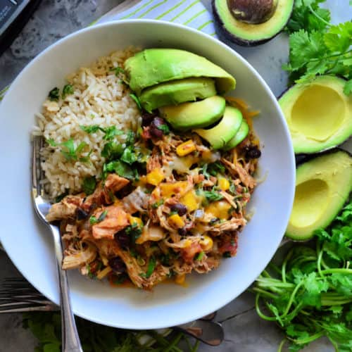 Bowl of rice with chicken, black beans, avocado and ingredients artistically next to bowl.