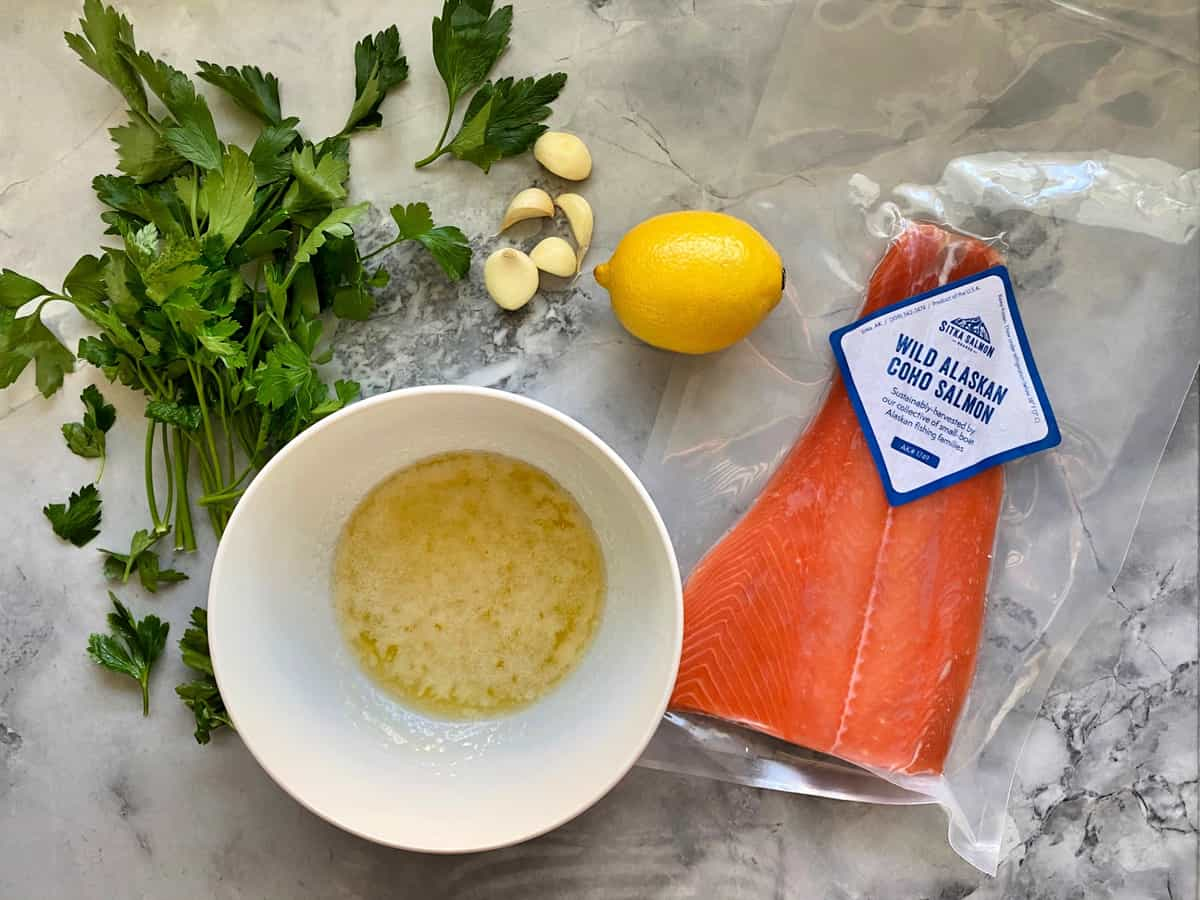Top view of packaged salmon, melted butter, garlic cloves, parsley, and whole lemon on countertop.