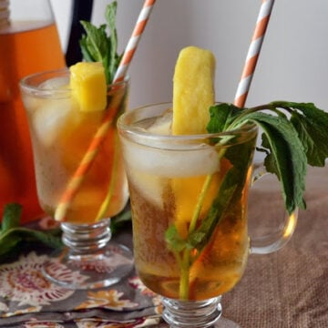 two sunday glasses with golden colored tea garnished with mango slices, mind, and paper straws.