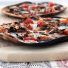 Side view of crisp Grilled Flatbread w/ Hot Italian Sausage, Peppers, & Caramelized Onions.