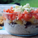 Side view of 7 layer greek dip in glass bowl topped with tomato and cucumber.